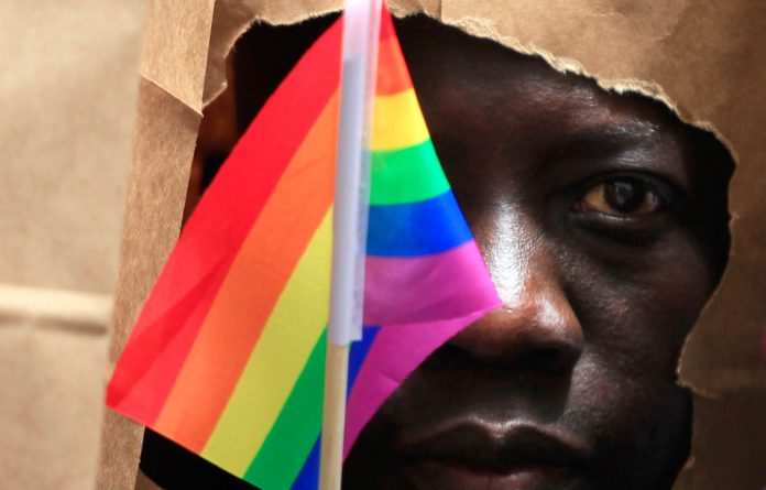 An asylum seeker from Uganda covers his face with a paper bag in order to protect his identity as he marches with the LGBT Asylum Support Task Force during the Gay Pride Parade in Boston.