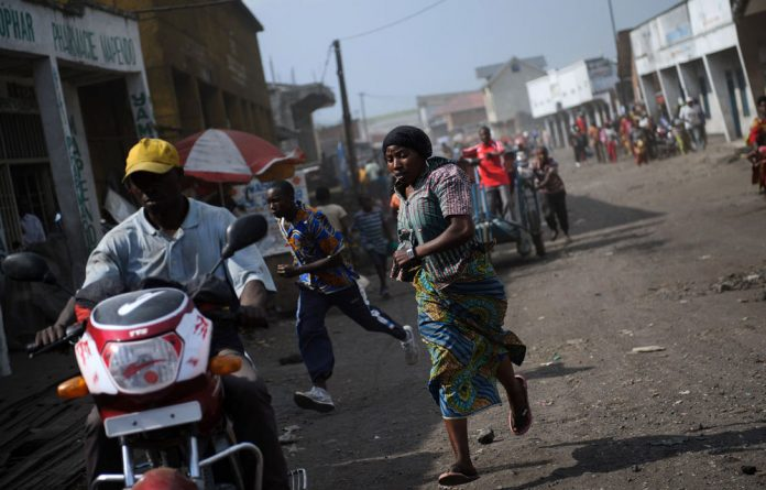 Residents run through the city following the sound of shell fire and gunshots in Goma