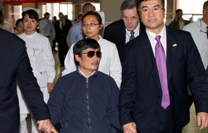 Blind lawyer Chen Guangcheng holds hands with US ambassador to China