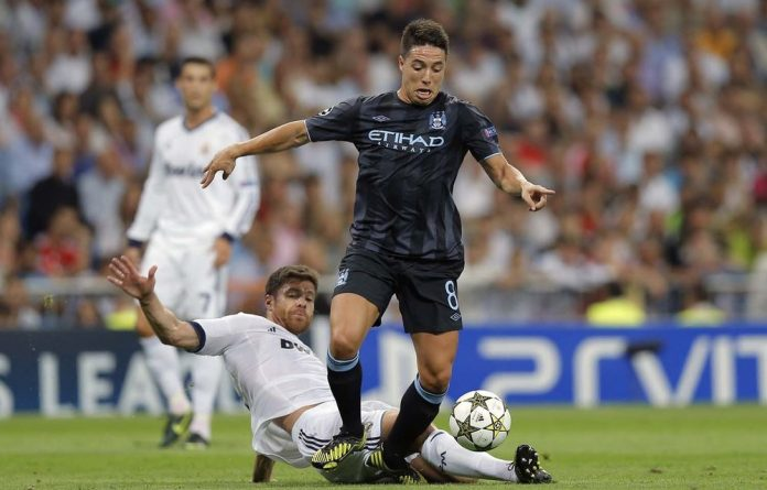 Real Madrid's Xabi Alonso duels for the ball with Manchester City Samir Nasri during a Champions League Group D soccer match at the Santiago Bernabeu Stadium
