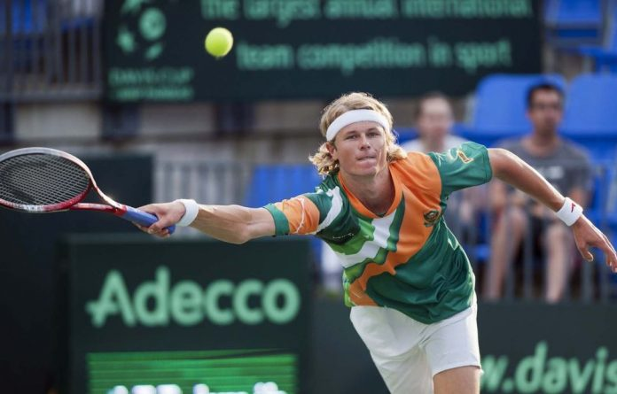 South Africa's Nikala Scholtz reaches for a return to Canada's Milos Raonic during a Davis Cup tennis match in Montreal.