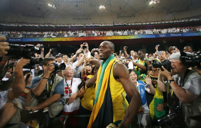 Catch me if you can: Usain Bolt swamped by photographers and fans after winning the 200m final at the Beijing Olympics.