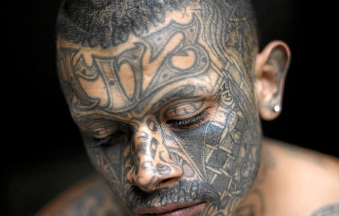 A Mara gang member who served time in a Guatemalan prison poses for a portrait to show off the tattoos he had acquired while serving his sentence in prison.
