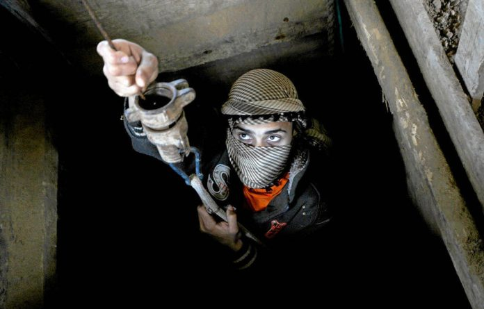 A Palestinian smuggler works inside a tunnel beneath the