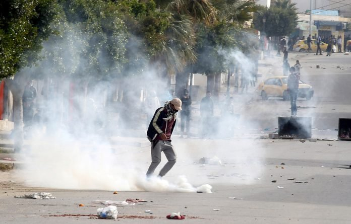 Tear gas is seen as protesters clash with riot police attempting to disperse the crowd during demonstrations