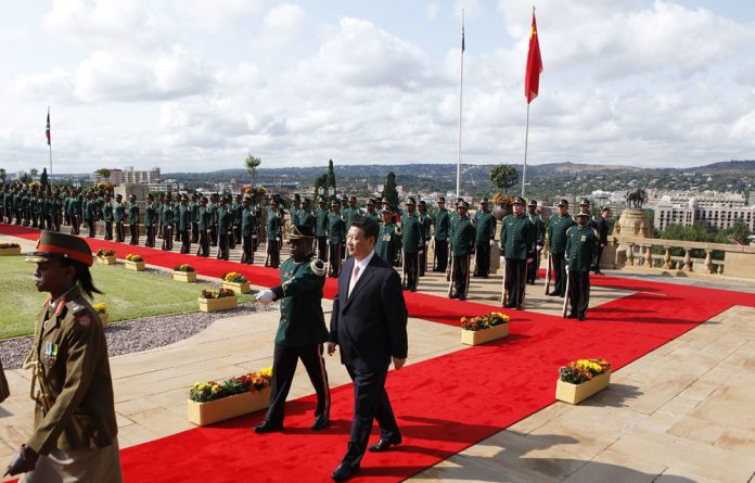 China's President Xi Jinping inspects a guard of honour in Pretoria. The need to consider China's development is redefining its role in Africa.
