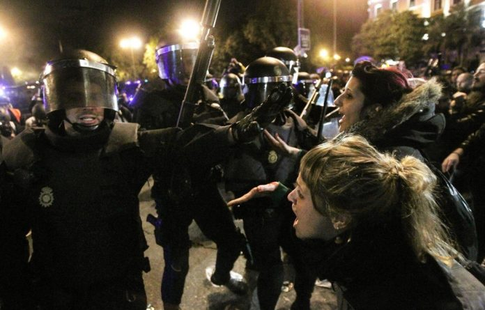 Police clash with protesters during a demonstration in front of Parliament in Madrid