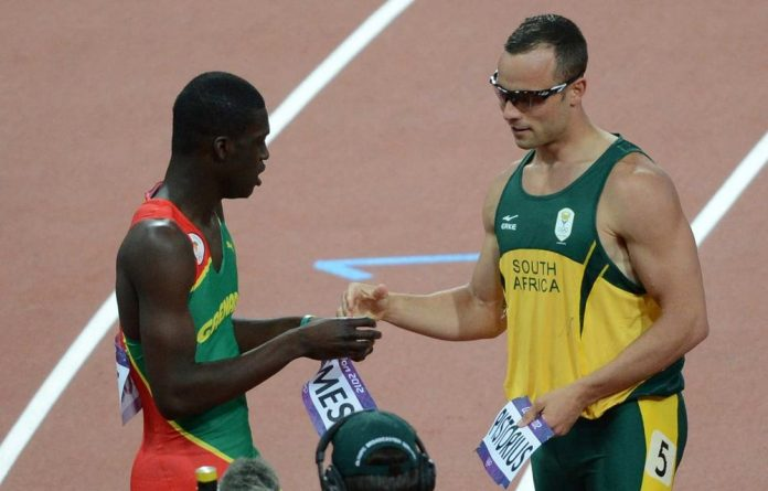 Oscar Pistorius and winner Kirani James swap pinned-on name labels.