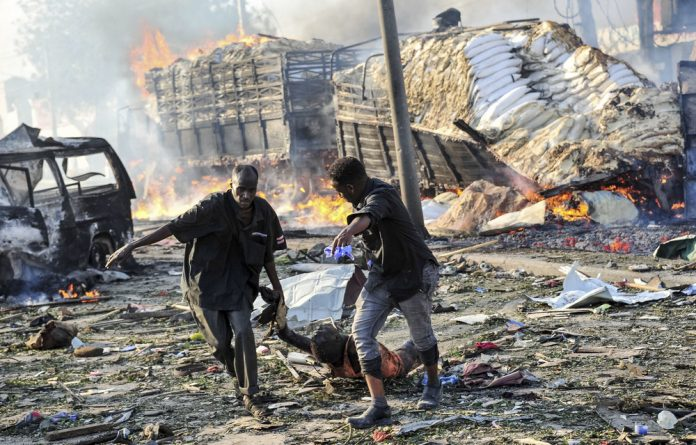 Two men drag the body of a person killed in the explosion of a truck bomb in the centre of Mogadishu.