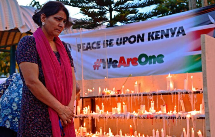 A woman pays her respects to the victims of the Westgate mall siege outside the shopping centre in Nairobi.