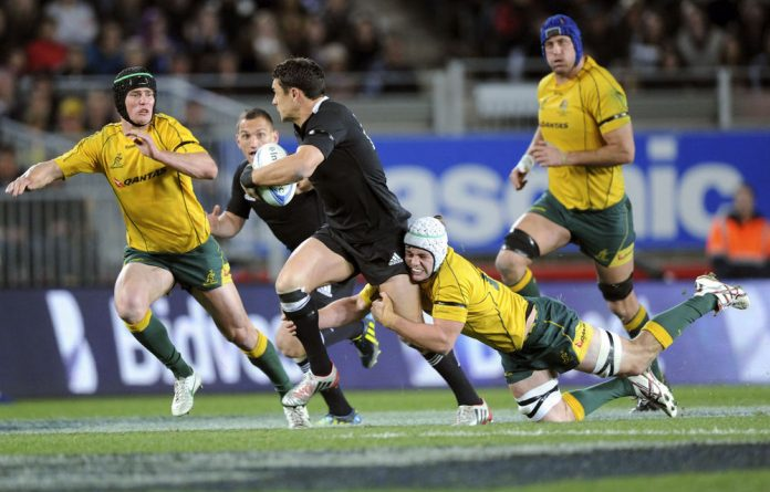 New Zealand's Dan Carter is tackled by Australia's Liam Gill during the Investec Rugby Championship at Eden Park in Auckland