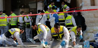 Members of the Israeli Zaka emergency response team clean blood from the scene of an attack at a Jerusalem synagogue on Tuesday.