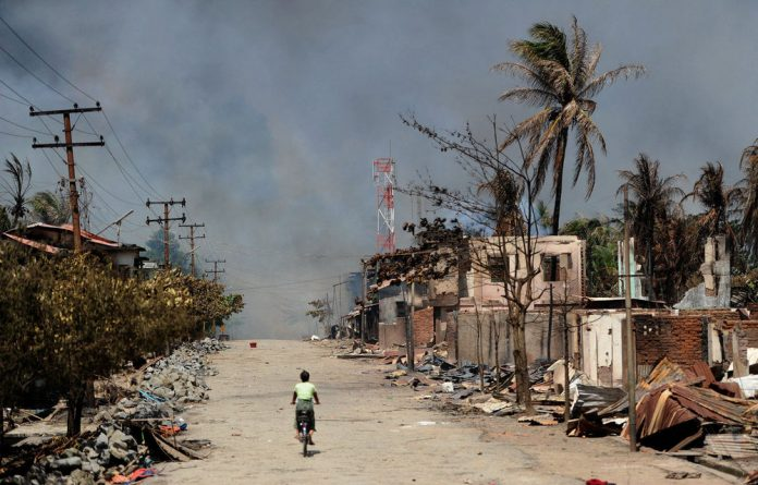 A resident rides her bicycle past burned houses amid ongoing violence in Sittwe