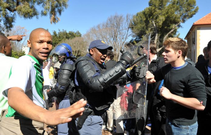 Breakup: Students and protesters clash at the University of the Free State in 2011. Police had to separate the opposing groups.