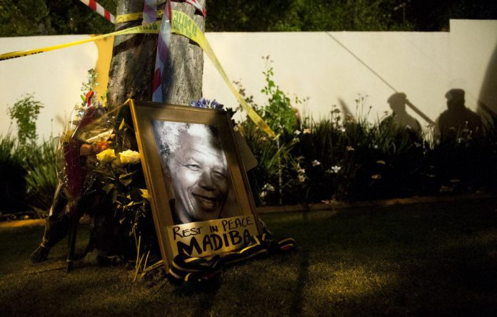 Mourners arrived in the early hours of Friday morning after hearing of Nelson Mandela's death carrying flowers and photographs.