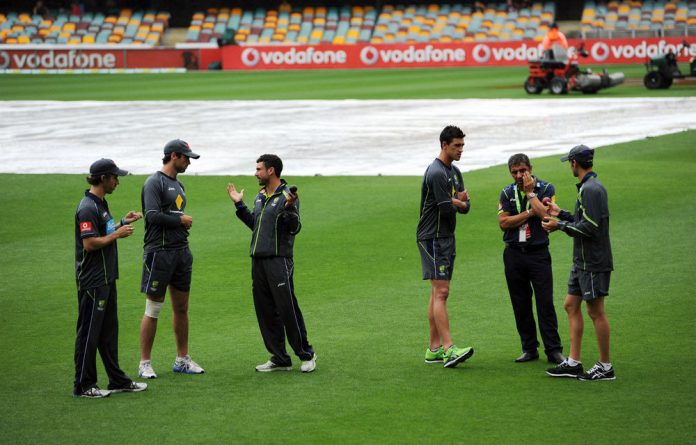 Australian cricketers inspect the Gabba ground in Queensland as play continues to be delayed by rain .