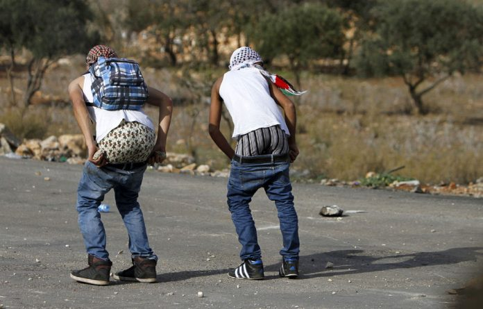 Palestinian stone-throwers pull down their pants in front of Israeli security forces during clashes near the West Bank city of Ramallah.