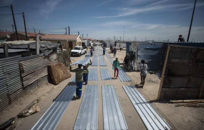 Residents receive a new shack building kit which comprises zinc sheets and other bits laid side by side.