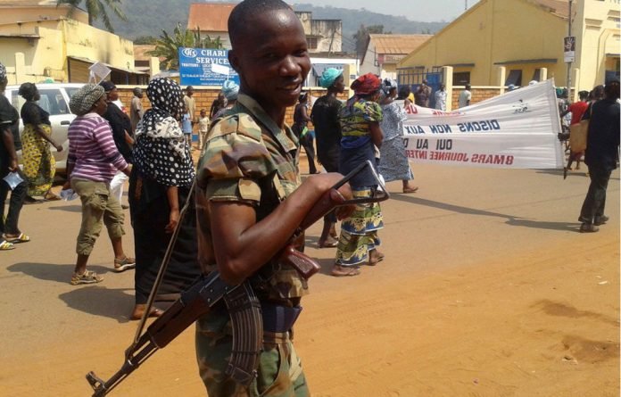 A soldier smiles as women march to protest against the conflict in their country in the streets of Bangui on Friday.