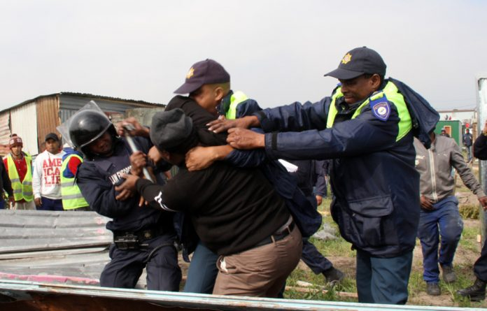 Police manhandle a shack dweller resisting the demolition of his home.