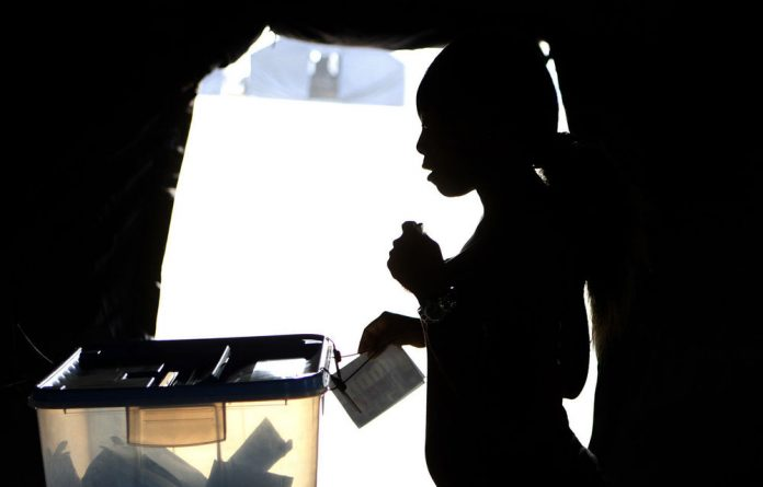 A woman casts her vote during the national elections in the capital Luanda