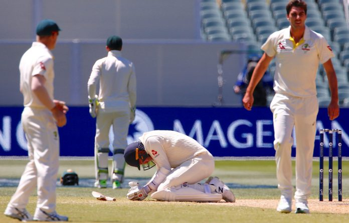 England's Craig Overton reacts after being hit by a delivery from Australia's Pat Cummins during the fifth day of the second Ashes cricket test match.