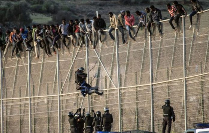 A penitentiary geography: A Spanish Civil Guard pulls an African migrant from a border fence between Morocco and Spain's North African enclave of Melilla.