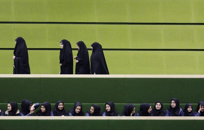 Iranian university students leave as school girls follow parliamentary debates in Tehran.