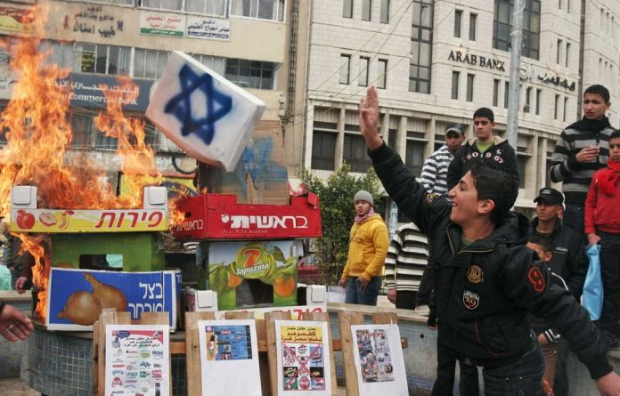 A file photograph from January 19 2009 shows Palestinians burning boxes of Israeli produce during a protest calling for a boycott of Israeli products after Israel's military operation in Gaza Strip