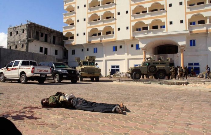 AMISOM stand guard by two bodies