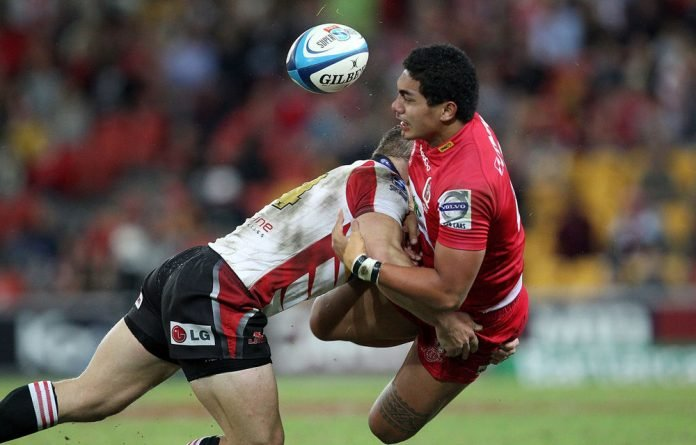 Chris F'Sautia of the Reds is tackled by Deon van Rensburg of the Lions.