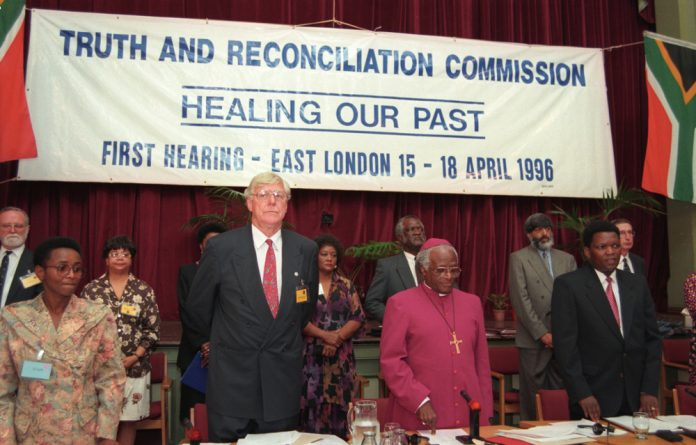 Archbishop Desmond Tutu and other members of the Truth and Reconciliation Commission at the first TRC hearing in East London in 1996. But the process of healing has not yet ended.