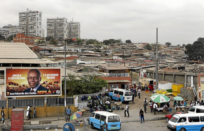 The optimistic oranges and yellows of an MPLA election poster are in stark contrast to the ramshackle reality and hardships ordinary people face in Luanda