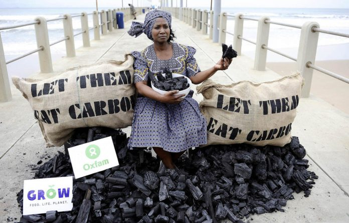 An activist from British charity Oxfam pretends to eat a piece of coal as a protest aimed at COP17 in Durban on December 2011.