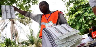 A man raises a ballot paper during the counting of governorship and state assembly election results in Lagos