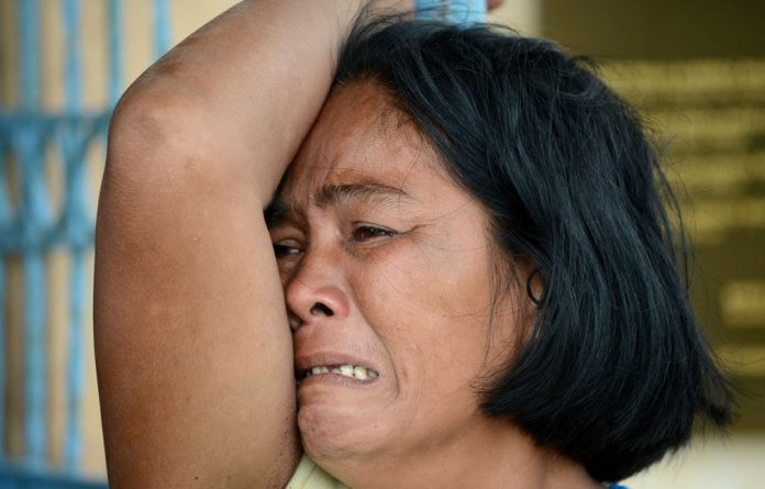 A woman mournes her dead son at a chapel in the aftermath of Typhoon Haiyan in Tacloban