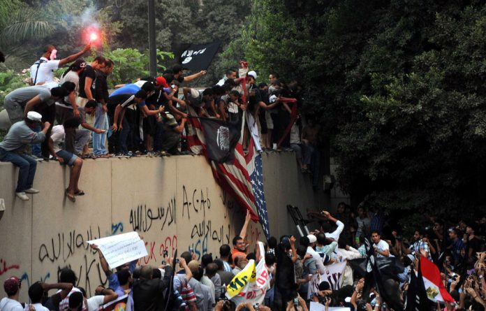 Egyptian protesters tear down the US flag and wave various black Islamic flags at the US embassy in Cairo during a demonstration against a film deemed offensive to Islam.