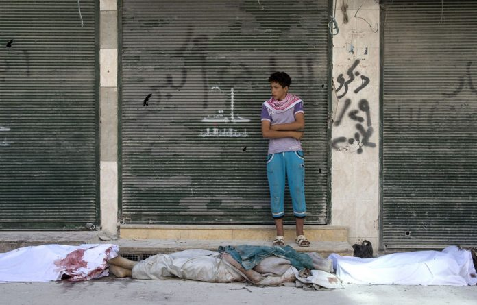 A Syrian boy stands next to three bodies close to a hospital