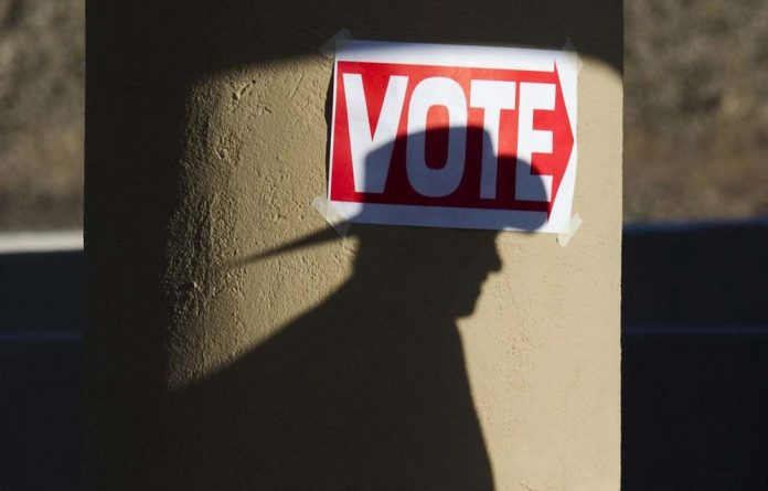 A shadow of a man wearing a cowboy hat falls on a pillar as he enters the polling place at Wickenburg Community Centre in Wickenburg