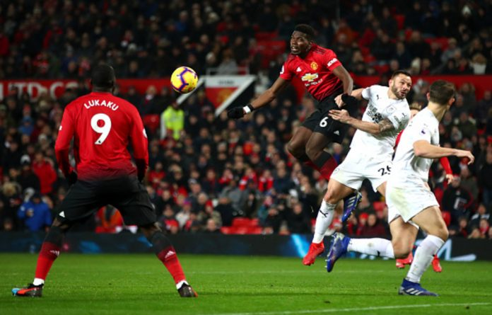 Paul Pogba of Manchester United wins a header under pressure from Phillip Bardsley of Burnley during the Premier League match between Manchester United and Burnley at Old Trafford on January 29 in Manchester.