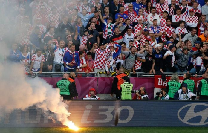 Croatian fans cheering after a flare was thrown onto the pitch during the Euro 2012 soccer championship Group C match between Italy and Croatia in Poznan