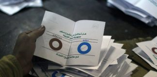 Polling station officials deposit ballots during the second round of a referendum on a new draft constitution in Egypt.