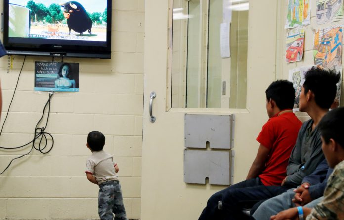 A detained immigrant child watches a cartoon at a U.S Customs and Border patrol immigration detainee processing facility.