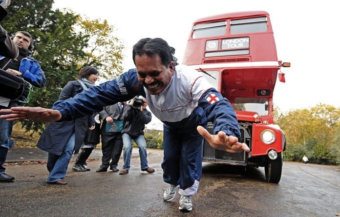 Strongman Manjit Singh pulls a double decker bus using ropes attached to his hair. On Thursday he will attempt to lift more than 23.5kg using only his eye sockets.