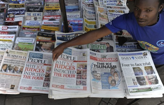 A newspaper vendor sells the day's papers carrying in the headlines photos of four Kenyans to face charges of crimes against humanity before the International Criminal Court