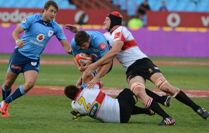 Franco van der Merwe and Willie Wepener of the Lions tackles Jono Ross of the Bulls during the Absa Currie Cup match between Vodacom Blue Bulls and MTN Golden Lions.