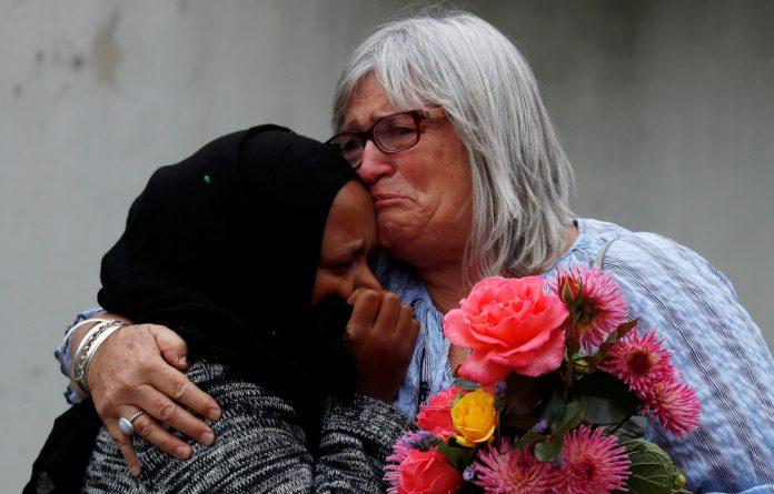 Women embrace near Masjid Al Noor mosque in Christchurch