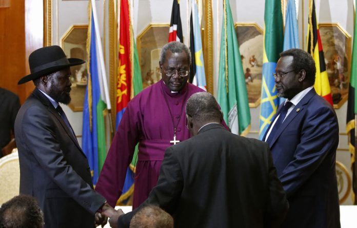 South Sudanese President Salva Kiir and rebel leader Riek Machar pray together after signing ceasefire.