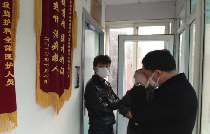 Friends of human rights activist Cao Shunli outside the intensive care unit in Beijing on March 1 2014. Shunli died in detention.