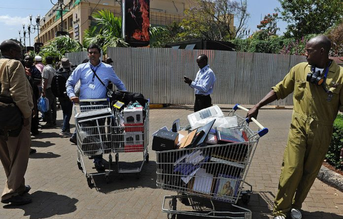 Workers salvage supermarket carts filled with goods from the wreckage at Westgate mall.
